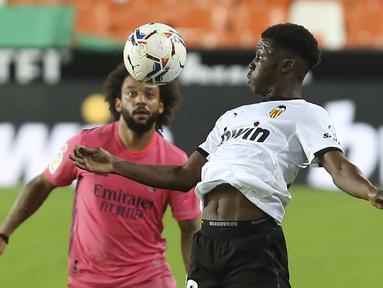 Gelandang Valencia, Yunus Musah berebut bola dengan bek Real Madrid, Marcelo berebut bola pada lanjutan La Liga di Stadion Mestalla, Selasa (9/11/2020) dinihari WIB. Real Madrid kalah telak 1-4 dari tuan rumah Valencia. (AP Photo/Alberto Saiz)