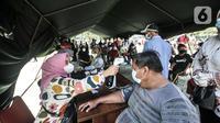 Petugas mengukur suhu warga penerima vaksin Covid-19 saat program Vaksinasi Keliling di RPTRA Pulo Besar, Jakarta, Senin (12/7/2021). Pemprov DKI menggelar Vaksinasi Keliling dengan sistem jemput bola guna mempermudah pelayanan kepada masyarakat di area padat penduduk. (merdeka.com/Iqbal S Nugroho)