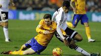 Pemain Barcelona, Lionel Messi, terjatuh saat berebut bola dengan pemain Valencia, Danilo Barbosa, pada laga La Liga Spanyol di Stadion Mestalla, Spanyol, Sabtu (5/12/2015). (AFP Photo/Jose Jordan)