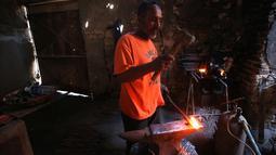 Seorang pekerja membentuk besi di sebuah bengkel di Baghdad, Irak (20/2). Para pandai besi ini bekerja untuk membuat pasak tenda dan alat-alat pertanian. (AFP Photo/Ahmad Al-Rubaye)
