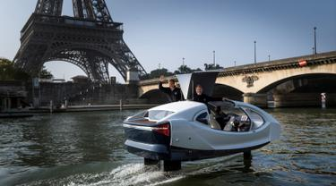 "Pendiri Sea Bubbles Alain Thebault (kiri) dan Anders Bringdal (kanan) berdiri di atas kapal ""flying taxi"" Sea Bubble saat demonstrasi di sungai Seine di Paris, Prancis (20/5). (AFP Photo/Lionel Bonaventure)"