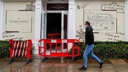 Seorang pria yang mengenakan masker berjalan melewati toko yang baru direnovasi di London, 13 Oktober 2020. Pasar tenaga kerja di Inggris yang terus terpukul akibat dampak pandemi COVID-19 diperkirakan akan membuat lebih banyak orang kehilangan pekerjaan pada musim dingin nanti. (Xinhua/Han Yan)