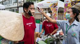 Seorang staf memeriksa suhu seorang penjual dalam festival kuliner di kota tua Phuket, Thailand (13/9/2020). Festival selama dua hari itu digelar untuk mendorong pariwisata dan perekonomian setempat. (Xinhua/Zhang Keren)