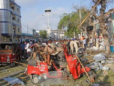 Warga berkumpul di lokasi ledakan di luar Hotel Weheliye, Jalan Maka al Mukaram, Mogadishu, Somalia, (22/3). Sedikitnya 14 orang tewas dan 10 lainnya terluka dalam ledakan bom mobil tersebut. (AP Foto/Farah Abdi Warsameh)