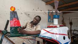 Felix Kambwiri menunjukkan bagian sayap dari helikopter buatannya di garasi rumahnya di Desa Gobede, Malawi, 19 Februari 2016. Helikopter yang dikerjakan sejak empat bulan lalu itu dibuat dari rongsokan besi tua dan fiberglass. (Amos Gumulira/AFP)