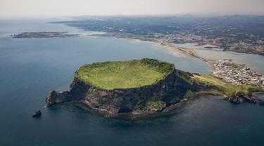 Pemandangan udara Seongsan Ilchulbong, atau 'Puncak Matahari Terbit', formasi batuan vulkanik di pulau Jeju, Korea Selatan (10/5/2019). Pulau Jeju adalah pulau terbesar di Korea dan terletak di sebelah selatan Semenanjung Korea. (AFP Photo/Ed Jones)