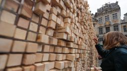 "Seorang perempuan mengambil sejumlah balok kayu dari "" The Disappearing Wall"" di Grand Place, Brussel, Belgia, 3 Oktober 2020. Instalasi seni memperingati 30 tahun reunifikasi Jerman itu terdiri dari 6.000 balok kayu dilengkapi kutipan seniman dan pemikir dari seluruh dunia. (Xinhua/Zheng Huansong)"