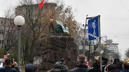 Sejumlah wartawan saat meliput seorang aktivis wanita gerakan hak perempuan Femen di tiang monumen Soviet di pusat kota Kiev, Ukraina (7/11). ). Aktivis tersebut menggelar aksi memperingati 100 tahun Revolusi Bolshevik. (AFP Photo/Genya Savilov)