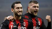 Pemain AC Milan, Hakan Calhanoglu dan Ante Rebic, melakukan selebrasi usai mencetak gol ke gawang Lazio pada laga Liga Italia di Stadion San Siro, Rabu (23/12/2020). AC Milan menang dengan skor 3-2. (AP/Luca Bruno)