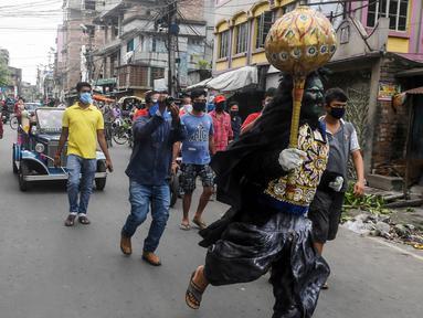 Seorang pria berkostum dewa kematian Yamaraj berlari keliling mencari warga yang masih berkeliaran tanpa masker di tengah lockdown di Kolkata, India (24/4/2020). Dalam aksinya, pria tersebut memberikan imbauan kepada warga agar memakai masker di tengah wabah virus corona. (AFP/Dibyangshu Sarkar)