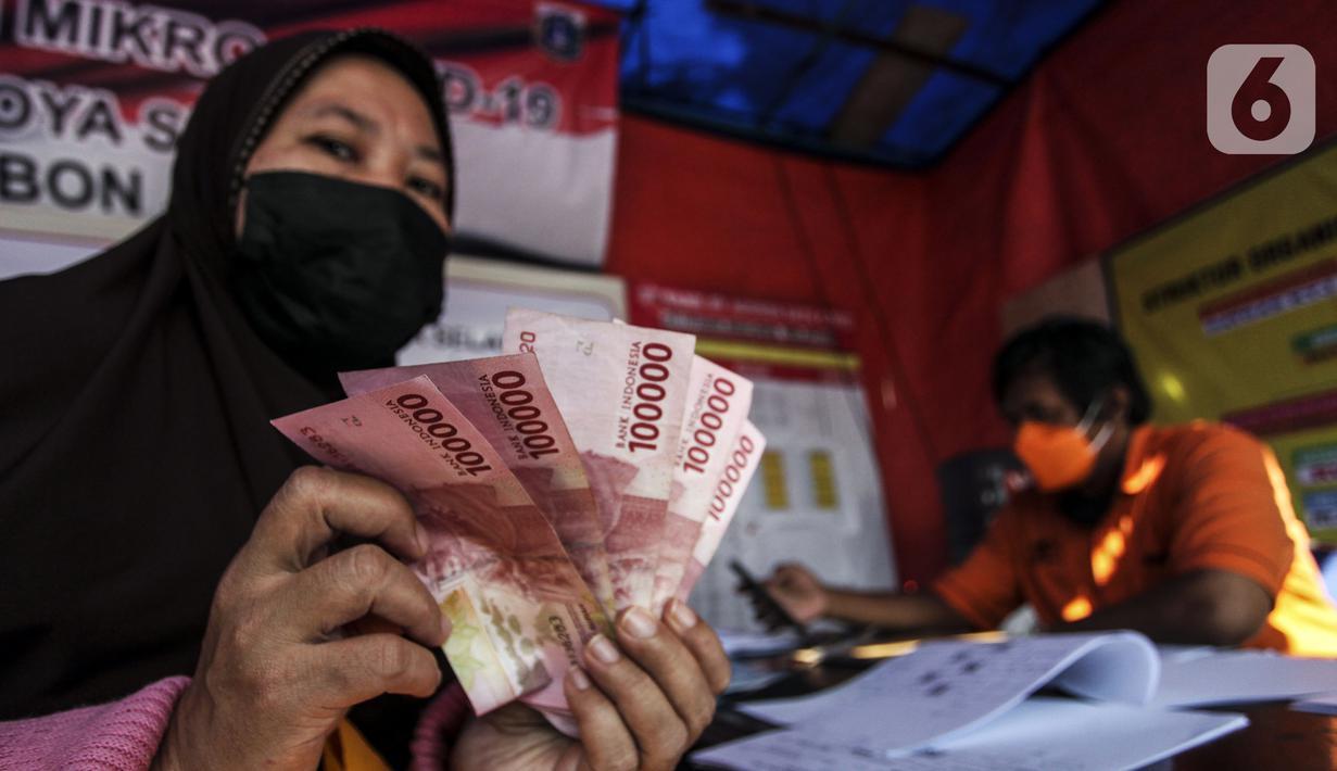 Warga menunjukkan uang bantuan sosial (bansos) di kawasan Kedoya Selatan, Jakarta Barat, Rabu (28/7/2021). Bansos berupa uang tunai sebesar Rp 600 ribu tersebut disalurkan oleh PT. Pos Indonesia. (Liputan6.com/Johan Tallo)
