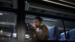 Wang Fan asal Tiongkok, berinteraksi dengan telepon selular saat berada di dalam bus usai pertandingan voli pantai putri Olimpiade Tokyo 2020 melawan Brasil, Selasa (27/7/2021). (Foto: AP/Felipe Dana)