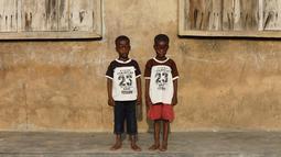 Si kembar identik, Taiwo Ahmed dan Kehinde Ahmed berpose di Igbo Ora, Negara Bagian Oyo, Nigeria pada 4 April 2019. Sebuah studi tahun 1970-an yang dilakukan oleh ilmuan Inggris menemukan bahwa sekitar 50 pasang anak kembar lahir dari setiap 1.000 kelahiran di Igbo Ora. (REUTERS/Afolabi Sotunde)