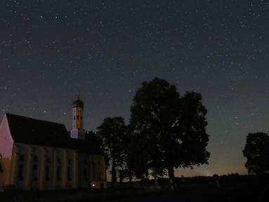 Sebuah meteor melintas di tengah langit malam selama hujan meteor tahunan Perseid di belakang gereja ziarah Sankt Coloman, barat daya Jerman, Minggu (12/8). Puncak hujan meteor terjadi pada 11-12 Agustus dan 12-13 Agustus. (KARL-JOSEF HILDENBRAND/DPA/AFP)