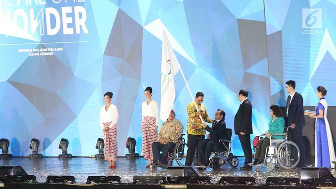 Gubernur DKI Jakarta Anis Baswedan menyerahkan bendera Asian Paralympic Committe kepada Presiden Para Committe Majid Rashed saat Penutupan Asian Para Games 2018  Stadion Madya, Gelora Bung Karno, Jakarta, Sabtu (13/10). (merdeka.com/Imam Buhori)