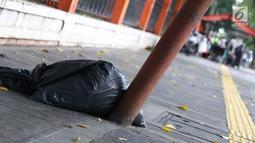 Kondisi tiang yang miring di Jalan Gedung Kesenian, Jakarta, Jumat (22/2). Keberadaan tiang miring tersebut membahayakan keselamatan pejalan kaki karena kabel yang turut menjuntai hingga ke bawah. (Liputan6.com/Immanuel Antonius)