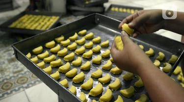 Pekerja menata adonan kue kering untuk dipanggang dalam oven di usaha pembuatan kue Pusaka Kwitang di kawasan Kwitang, Jakarta Pusat, Selasa (27/4/2021). Pada masa pandemi COVID-19, usaha milik Hasanudin ini masih memenuhi stok walau tidak banyak permintaan dari para agen. (merdeka.com/Imam Buhori)