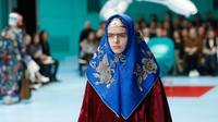 Seorang model dengan scarf menyerupai hijab di kepalanya menampilkan koleksi terbaru Gucci FW18 dalam Milan Fashion Week 2018, Rabu (21/2). Hadirnya model yang memakai scarf menyerupai hijab itu mencuri perhatian. (AP Photo/Antonio Calanni)