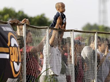 Seorang anak digendong bapaknya untuk melihat pemain Persija Jakarta latihan di Lapangan NYTC, Sawangan, Depok, Selasa (21/1/2020). Warga antusias melihat punggawa Macan Kemayoran berlatih. (Bola.com/M Iqbal Ichsan)