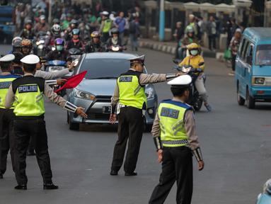 Petugas polisi lalu lintas memberi arahan kepada pengguna mobil saat pemberlakuan sistem ganjil genap di pintu masuk Gardu Tol Cibubur 2, Jakarta, Senin (16/4). (Liputan6.com/Faizal Fanani)