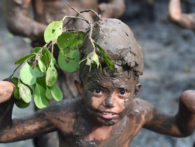 Seorang bocah berpose saat tradisi mandi lumpur atau mebuug-buugan di Desa Kedonganan, Denpasar, Bali, Jumat (8/3). Tradisi ini diadakan sehari setelah Hari Raya Nyepi. (Sonny Tumbelaka/AFP)