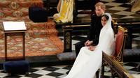 Pangeran Harry duduk bersama Meghan Markle saat prosesi pernikahan mereka di Kapel St. George, Kastil Windsor, Inggris, Sabtu (19/5). Pangeran Harry dan Meghan Markle resmi menjadi suami istri. (Owen Humphreys/POOL/AFP)