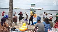 Sejumlah pengunjung bermain air di Beach Pool Ancol, Jakarta, Selasa (25/12). Pasangnya air laut dan cuaca buruk mengakibatkan pantai Ancol sepi pengunjung saat libur Natal 2018. (Liputan6.com/Faizal Fanani)