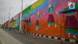 "Pekerja menyelesaikan pembuatan mural di Flyover Gaplek, Tangerang Selatan, Rabu (10/3/2021). Konsep muralnya adalah ""Tangsel Membangun"". (Liputan6.com/Faizal Fanani)"