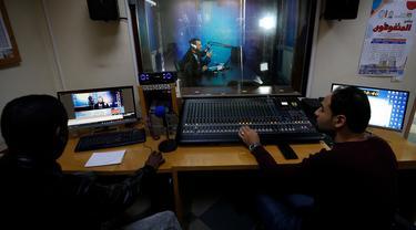 Teknisi membantu guru yang melakukan siaran di sebuah stasiun radio pendidikan di Jalur Gaza, Palestina, Minggu (15/3/2020). Di tengah kebijakan isolasi untuk mencegah penyebaran virus corona COVID-19, guru di Jalur Gaza menyampaikan materi pelajaran melalui siaran radio. (MOHAMMED ABED/AFP)
