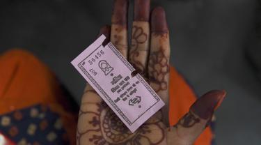 Seorang perempuan yang bepergian dengan bus  New Delhi Transport Corporation menunjukkan tiket berwarna merah muda untuk memanfaatkan skema naik gratis di New Delhi, 29 Oktober 2019. Perjalanan bebas biaya untuk wanita di bus umum Ibu Kota India telah dimulai pada 29 Oktober. (Sajjad HUSSAIN/AFP)