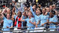 Para pemain Manchester City merayakan gelar juara Piala FA setelah mengalahkan Watford pada laga final di Stadion Wembley, London, Sabtu (18/5). City menang 6-0 atas Watford. (AFP/Glyn Kirk)