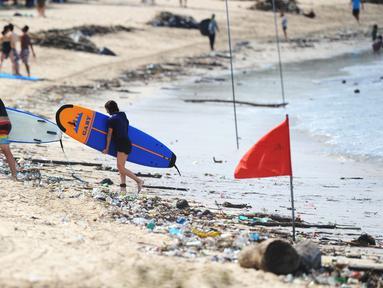Turis berjalan dengan papan selancar melintasi puing-puing dan sampah di pesisir Pantai Kuta, Bali, Minggu (9/12). Kawasan pantai Kuta kembali dipenuhi oleh sampah hanyut terbawa oleh gelombang. (SONNY TUMBELAKA / AFP)