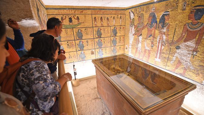 Wisatawan melihat sarkofagus emas dinasti ke-18 Firaun Tutankhamun (1332–1323 SM), ditampilkan di ruang pemakamannya di makam bawah tanahnya (KV62) di Lembah Para Raja, Luxor, Mesir (31/1). (AFP Photo/Mohamed El-Shahed)