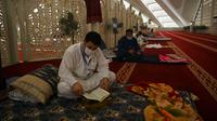 Pria Muslim (kiri) membaca Alquran saat beritikaf di Masjid Agung Faisal di Islamabad, Pakistan, Kamis (14/5/2020). Itikaf adalah berdiam diri di masjid dengan niat beribadah untuk mendekatkan diri kepada Allah swt pada sepuluh hari terakhir bulan Ramadan. (Aamir QURESHI/AFP)