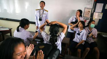 Seorang guru tunanetra, Damkerng Mungthanya tersenyum ketika para siswa menyanyikan lagu untuknya di sekolah Satri Si Suriyothai di Bangkok, 15 Februari 2019. Damkerng merupakan guru Bahasa Inggris di Sekolah Menengah.  (REUTERS/Athit Perawongmetha)