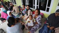 Pengungsi bencana tsunami beristirahat di sebuah masjid di Tenjolahang, provinsi Banten, Rabu (26/12). Data sementara jumlah korban dari bencana tsunami Selat Sunda tercatat lebih dari 400 orang meninggal dunia. (Sonny TUMBELAKA / AFP)