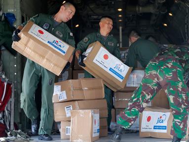 Personil militer Jepang dibantu TNI mengangkut bantuan logistik untuk korban gempa dan tsunami dari sebuah pesawat kargo Angkatan Udara Jepang di bandara Mutiara Sis Al-Jufri di Palu, Sulawesi Tengah, Indonesia (6/10). (AP Photo/Tatan Syuflana)