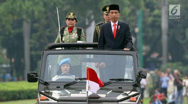 Presiden Joko Widodo (Jokowi) melakukan inspeksi pasukan saat apel bersama Wanita TNI, Polwan dan segenap wanita komponen bangsa di Lapangan Silang Monas, Jakarta, Rabu (25/4). Apel digelar guna memperingati Hari Kartini 2018. (Liputan6.com/Johan Tallo)