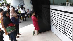 Keluarga melihat daftar korban luka tsunami Selat Sunda karyawan RSUD Tarakan di RSUD Tarakan, Jakarta, Selasa (24/12). Sebanyak 20 orang di antaranya adalah karyawan RS Tarakan, sementara sisanya anggota keluarga. (Liputan6.com/Herman Zakharia)