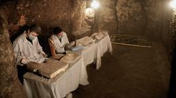 Arkeolog meneliti patung-patung dan artefak yang ditemukan di dalam sebuah makam kuno dekat piramida terkenal Mesir di Saqqara, Giza, Sabtu (10/11). Puluhan mumi kucing dan koleksi langka scarab telah ditemukan di tujuh sarkofagus. (AP/Nariman El-Mofty)
