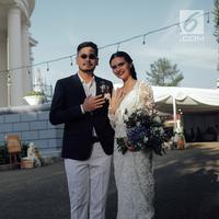 Penyanyi Petra Sihombing menunjukkan cincin pernikahannya dengan Firrina Sinatrya usai pemberkatan di GPIB Immanuel, Jakarta, Jumat (23/3). Petra resmi mempersunting Firrina yang dipacarinya selama dua tahun. (Liputan6.com/Faizal Fanani)