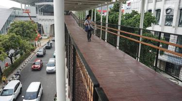 Warga melintasi jembatan penyeberangan (Skybridge) yang menghubungkan Stasiun LRT Velodrome dengan Halte Transjakarta Pemuda di Rawamangun, Jakarta, Senin (29/7/2019). Skybridge ini bertujuan memudahkan integrasi penumpang LRT menuju Transjakarta atau sebaliknya. (Liputan6.com/Immanuel Antonius)