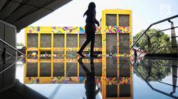 Seorang wanita melihat karya seni pemural Kolombia Diana Ordonez di TIM, Jakarta, Selasa (11/9). Mural tersebut dibuat untuk mempererat kerjasama antara Pemprov DKI dengan Kedutaan Besar Kolombia dalam bidang seni perkotaan. (Liputan6.com/Faizal Fanani)