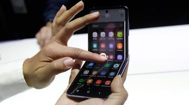 Seorang pekerja Samsung mendemonstrasi Galaxy Z Flip pada acara Unpacked 2020 di San Francisco, Selasa (11/2/2020). Menjadi perangkat kedua dengan layar lipat karyanya, Samsung menghadirkan perbedaan desain pada Galaxy Z Flip jika dibandingkan ponsel generasi pertama, Galaxy Fold. (AP/Jeff Chiu)