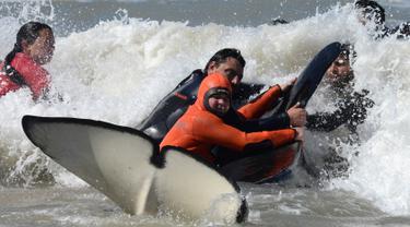 Tim penyelamat dan sukarelawan berupaya mengembalikan paus pembunuh ke laut setelah terdampar, di pantai Mar Chiquita, Argentina, Senin (16/9/2019). Sebanyak enam dari tujuh paus pembunuh yang ditemukan terdampar berhasil dikembalikan ke laut, tetapi satu di antara mereka mati. (AP/Marina Devo)