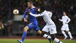 Gelandang Islandia, Gylfi Sigurdsson, berusaha melewati gelandang Prancis, Blaise Matuidi, pada laga Kualifikasi Piala Eropa 2020 di Reykjavik, Sabtu (11/10). Islandia kalah 0-1 dari Prancis. (AFP/Jonathan Nackstrand)