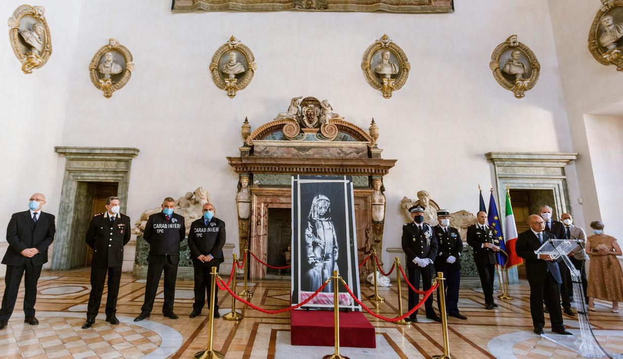 Lukisan seniman Inggris Banksy yang menggambarkan sosok perempuan muda dengan ekspresi sedih dikembalikan ke Duta Besar Prancis untuk Italia, Christian Masset (keempat kanan) setelah dicuri selama upacara di Kedutaan Besar Prancis di Roma (14/7/2020). (AP/Photo/Domenico Stinellis)