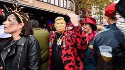 Seorang pria dengan topeng Donald Trump bersuka cita saat puluhan ribu orang menyambut dimulainya musim karnaval di jalan-jalan Kota Cologne, Jerman, Senin (11/11/2019). Tradisi ini akan dimulai tepat pada jam 11.11, tanggal 11, dan bulan sebelas. (AP Photo/Martin Meissner)