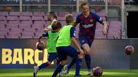 Gelandang Frenkie de Jong menggiring bola saat bermain dengan anak-anak selama pengenalan dirinya sebagai pemain baru Barcelona di stadion Camp Nou, Spanyol (5/7/2019). (AFP Photo/Lluis Gene)
