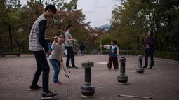 Keluarga memainkan permainan tradisional Korea selama perayaan Chuseok di desa hanok Namsan di Seoul (5/10). Perayaan Chuseok merupakan kesempatan orang Korea untuk pulang ke kampung halaman untuk berdoa ke leluhur. (AFP Photo/Ed Jones)